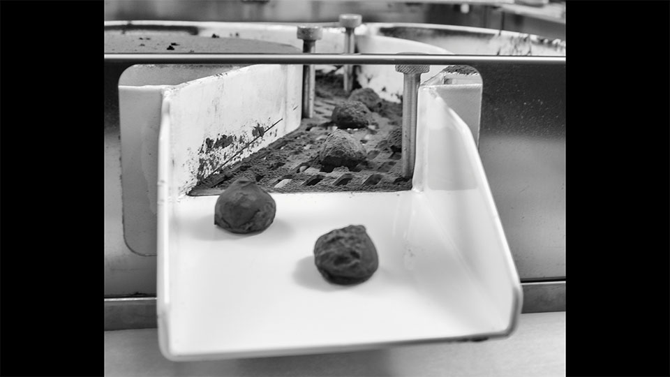 Automatic Truffle. Chocolate truffles coating machine: Details of exiting finished chocolate truffles