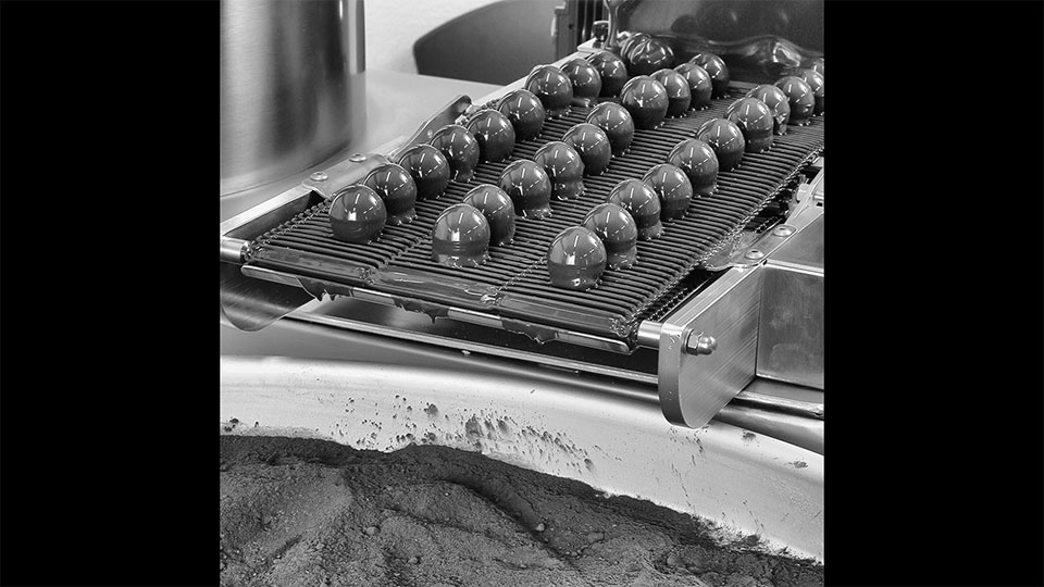 Truffle. Truffle chocolate coating machine: details of the hopper loading with cocoa powder